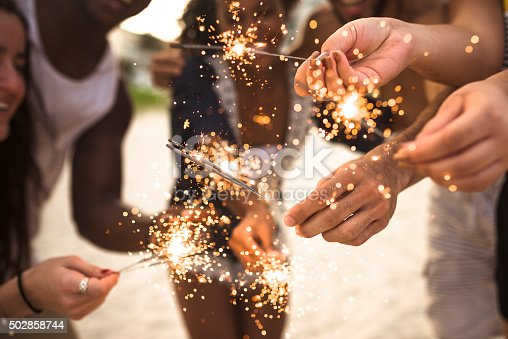 471113366istockphoto people celebrating the new year on the beach with sparkler 502858744
