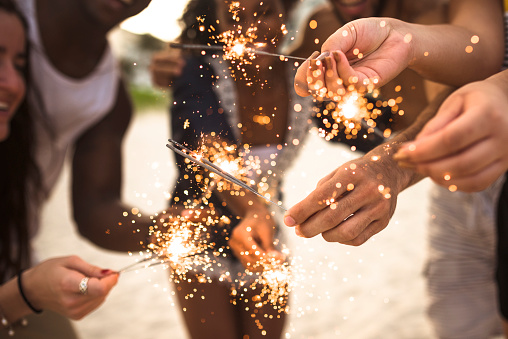 471113366 istock photo people celebrating the new year on the beach with sparkler 502858744