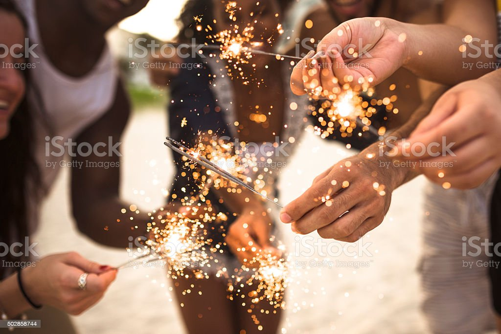people celebrating the new year on the beach with sparkler stock photo