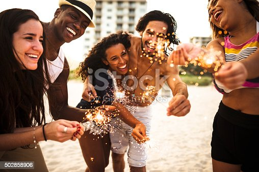471113366istockphoto people celebrating the new year on the beach with sparkler 502858906