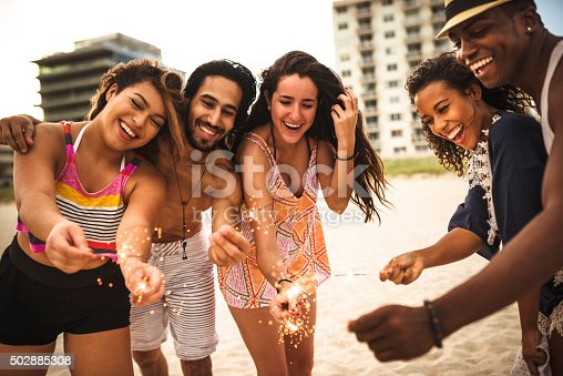 471113366istockphoto people celebrating the new year on the beach with sparkler 502885308