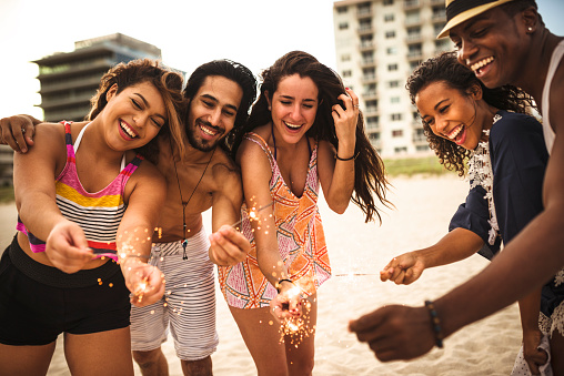 471113366 istock photo people celebrating the new year on the beach with sparkler 502885308