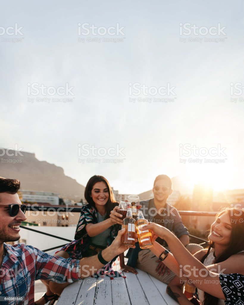 People celebrating with drinks at rooftop party stock photo