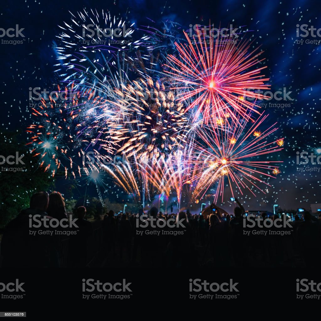 people cheering in front of vibrant firework silhouettes of human crowd cheering in front of vibrant firework under night sky 2018 Stock Photo