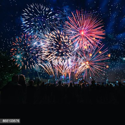istock people cheering in front of vibrant firework 855103576
