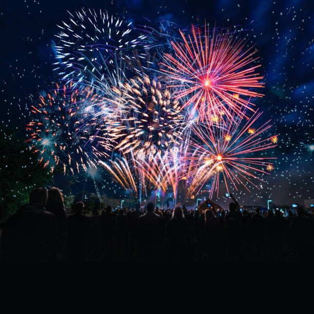 people cheering in front of vibrant firework stock photo