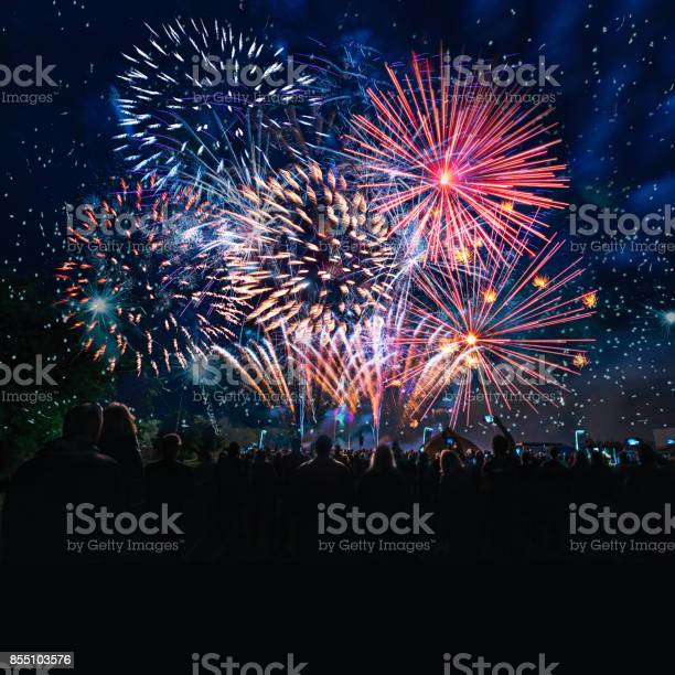 People Cheering In Front Of Vibrant Firework Stock Photo - Download Image Now