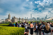 New York City, USA - May 14, 2016: People chilling on rooftop party with Manhattan and Central Park view of the Metropolitan Museum of Art in New York.