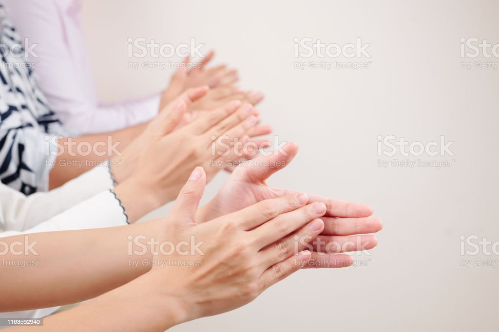 Close-up of group of business people clapping hands together while...