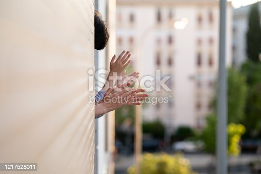 istock People clapping in the window in support of people who fight against the coronavirus 1217528011