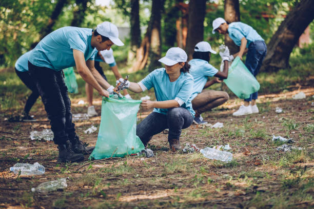 People cleaning the environment Group of people, cleaning together in public park, saving the environment. environmental cleanup stock pictures, royalty-free photos & images