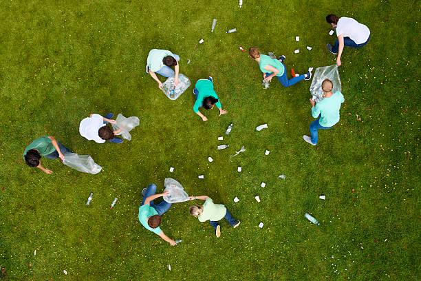 personnes nettoyage de litière sur de l'herbe - détritus photos et images de collection