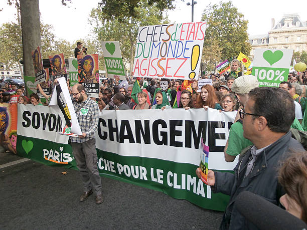 personnes climat mars à paris. - climat photos et images de collection