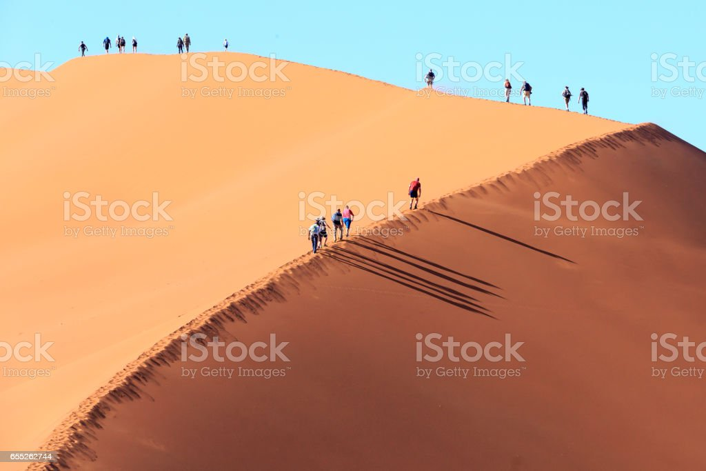 People climbing a dune in Sossusvlei Namibia stock photo