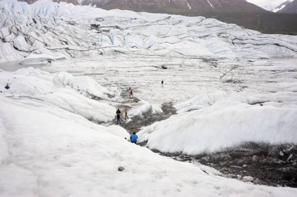 People climbing down into Matanuska Glacier in Alaska stock photo