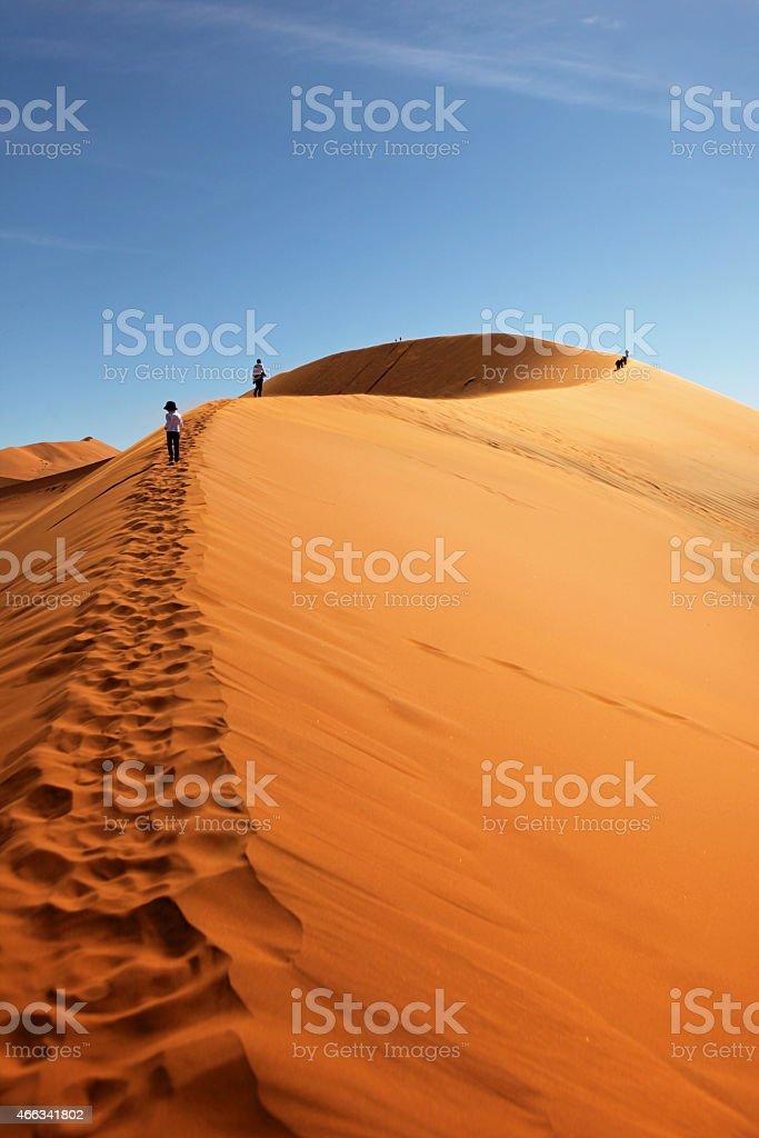 People Climbing Red Sand Dunes at Sossusvlei, Namibia stock photo