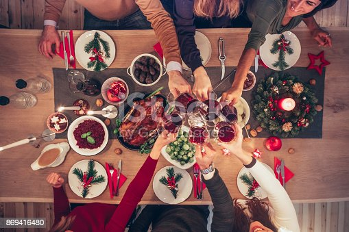 overhead view on people clinking wine glasses at christmas table with traditional german food