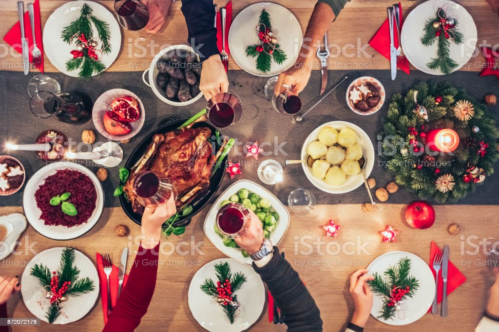 people clinking wine glasses at christmas table stock photo