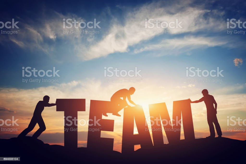 People connect letters to compose the team word. Teamwork concept,...