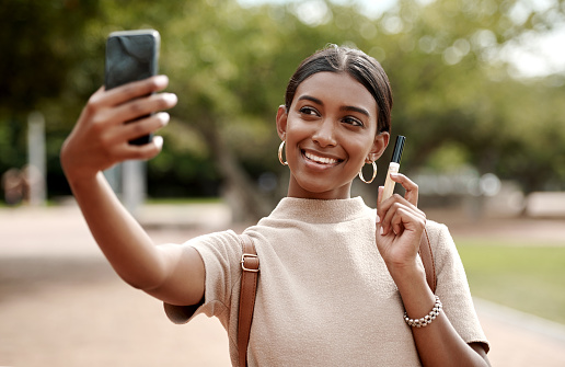 Shot of a young businesswoman taking selfies with a smartphone and holding a tube of lipgloss  against a city background