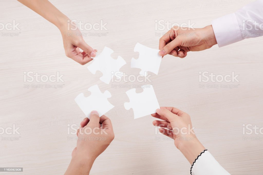 Close-up of group of people holding pieces of puzzles and connecting...