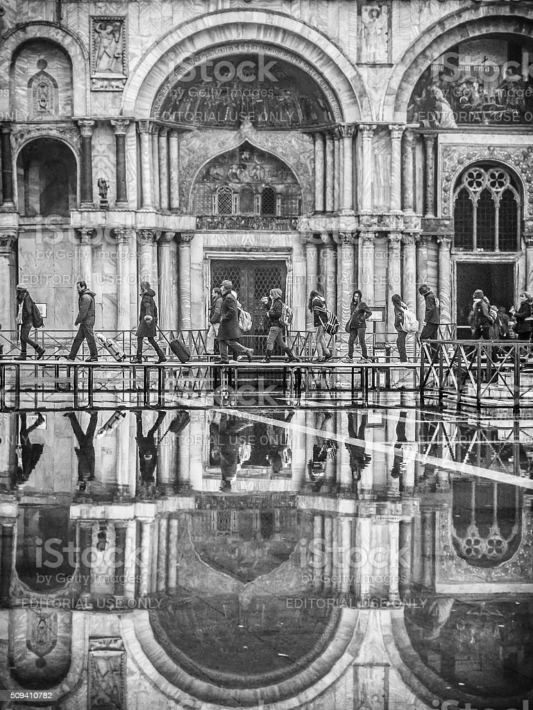 People crossing a flooded St Mark's Square on raised ptatforms stock photo
