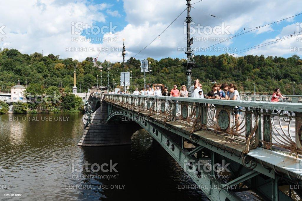 People crossing bridge in Prague stock photo