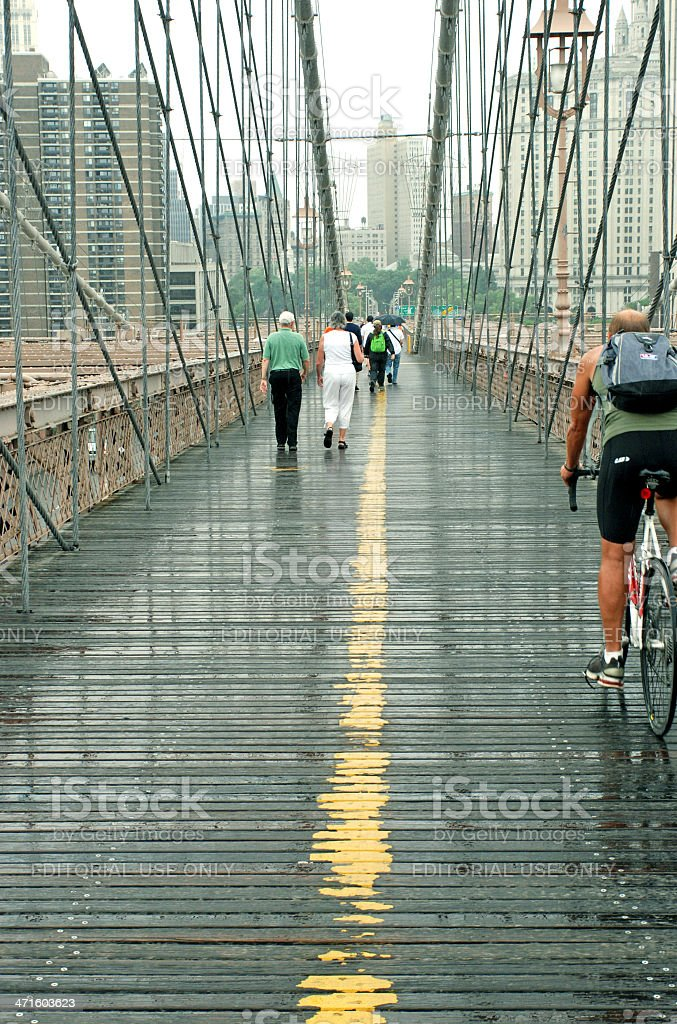 People crossing Brooklyn Bridge in rain royalty-free stock photo