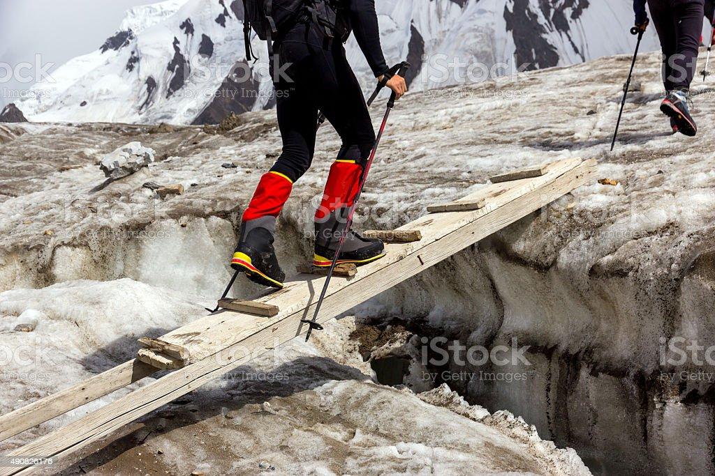 People Crossing Glacier Crevasse on Wood Shaky Footbridge stock photo