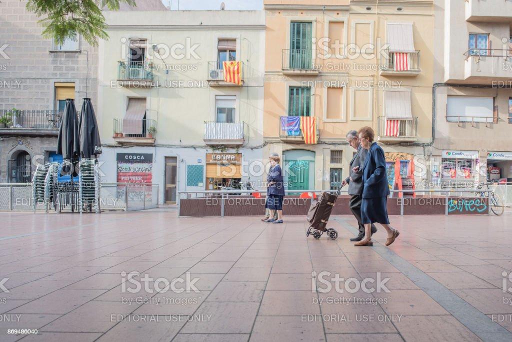 People crossing Plaza Del Revolucio in Gracia, Barcelona stock photo