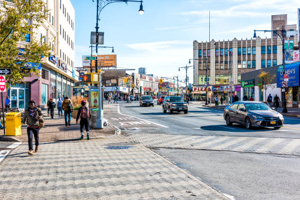 People crossing street in Fordham Heights center, New York City, NYC morning, cars, sunny day stock photo