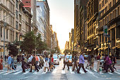 NEW YORK CITY - CIRCA 2017: Busy crowds of people cross the intersection of 5th Avenue and 23rd Street in Manhattan, New York City with the colorful setting sun in the background on June 3rd, 2017.