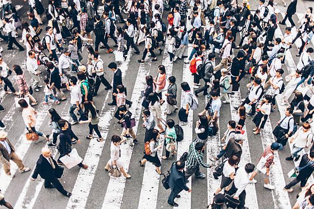 People crossing street on walkway stock photo