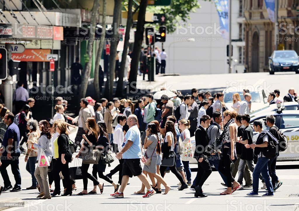 People crossing sunlit street stock photo
