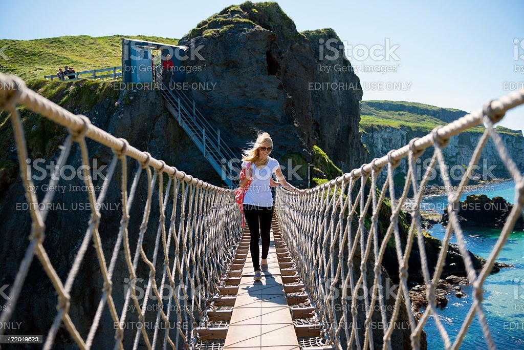 People crossing the Carrick-a-Rede Rope Bridge in County Antrim stock photo