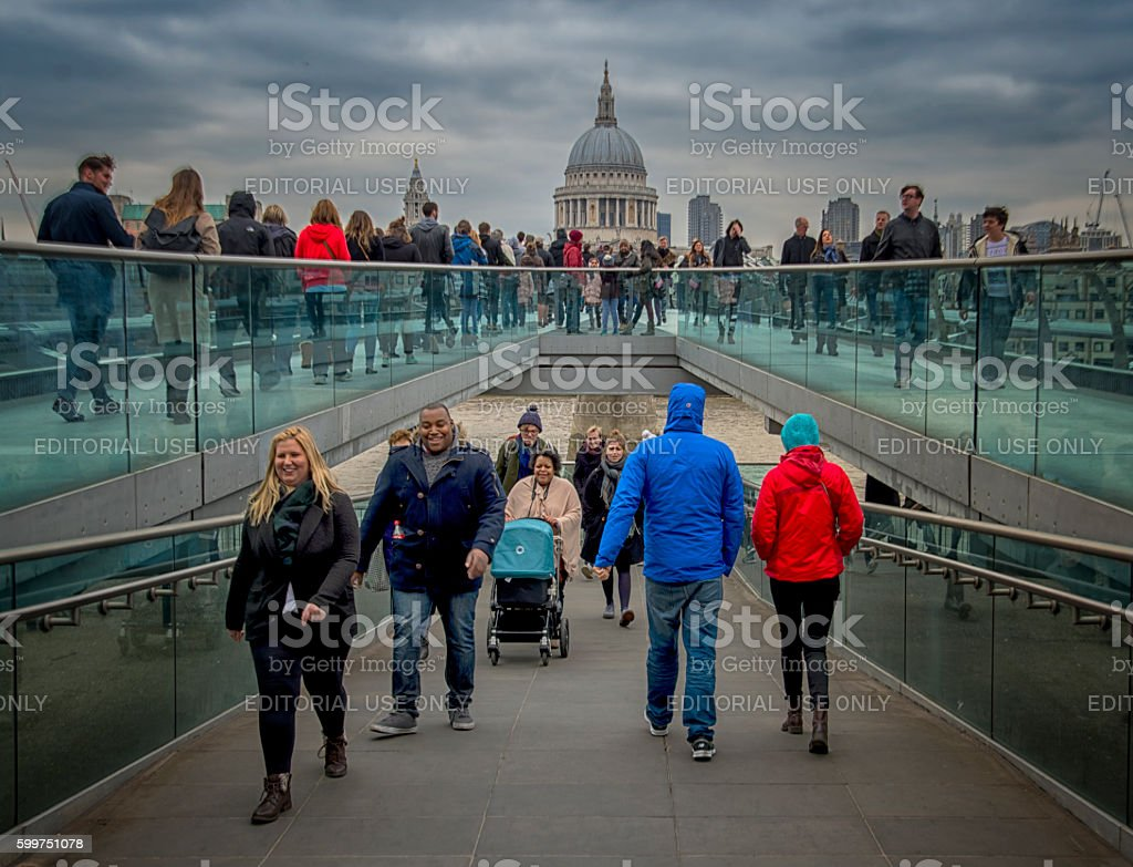 People crossing the London Millennium Footbridge stock photo