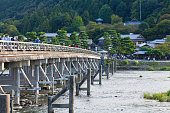 People crossing the Oi River on Togetsu-kyo Bridge in Kyoto, Japan