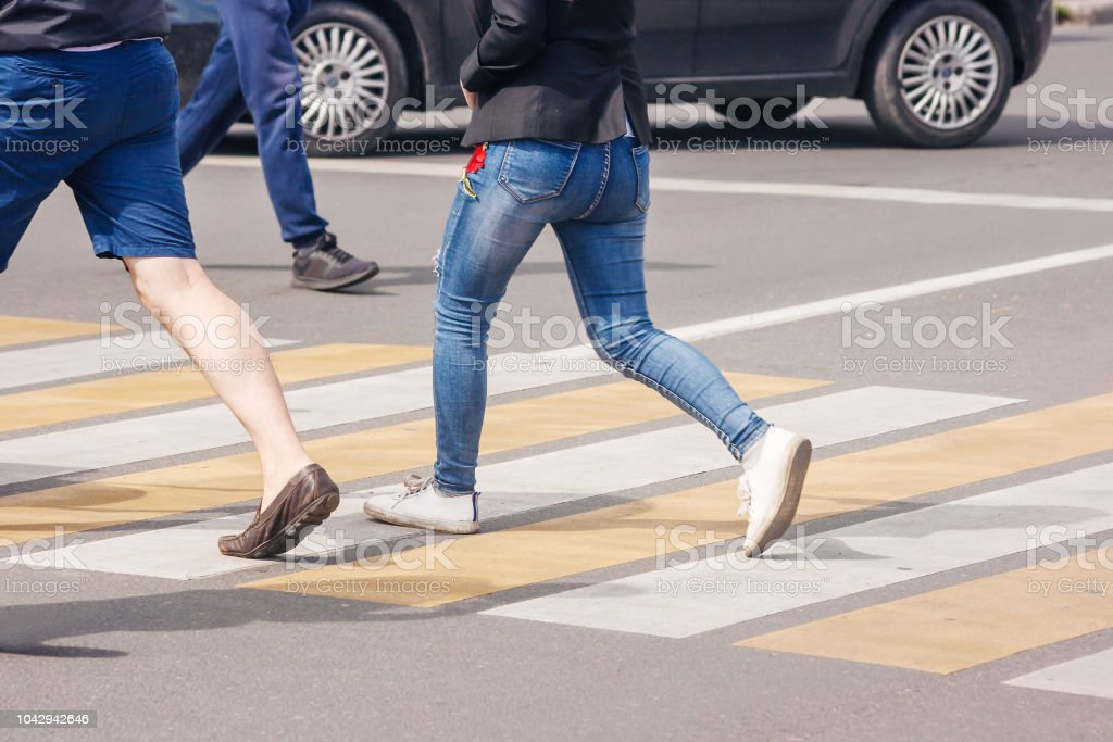 people crossing the pedestrian crossing on sunny summer day