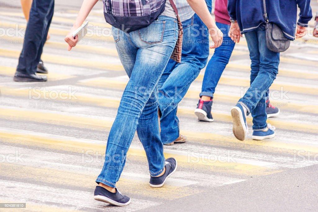 pedestrians walk on a pedestrian crossing on sunny summer day