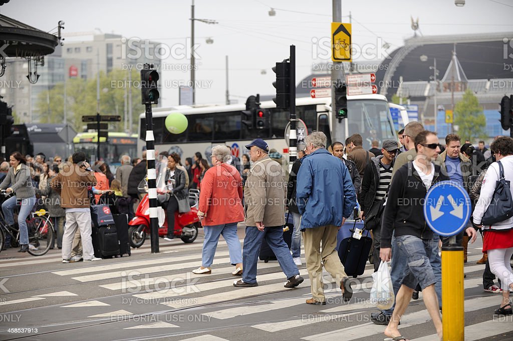 People crossing the street at Damrak, Amsterdam royalty-free stock photo
