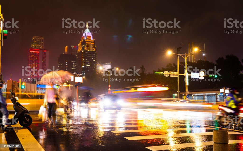 City view of Taipei with rain and abstract people crossing the street...