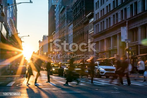Rays of sunlight shine on the busy people walking across an intersection in Midtown Manhattan in New York City NYC