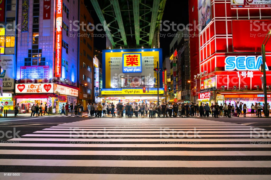 People Crossing the street in the Akihabara District of Tokyo, Japan at Night stock photo