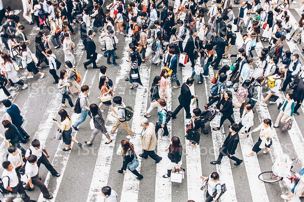 People crossing the street on walkway stock photo