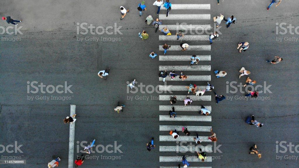 Aerial. Pedestrian crossing crosswalk and crowd of peolple.