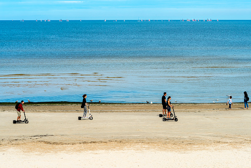 People cycling on scooters near a shore of sea in Jurmala