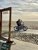 Santa Monica, USA - December 20, 2019: People cycling on the beach between Venice Beach and Santa Monica