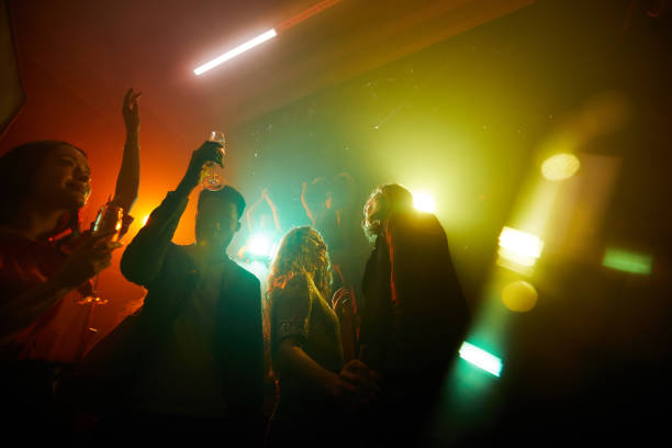 People dancing in disco lights stock photo