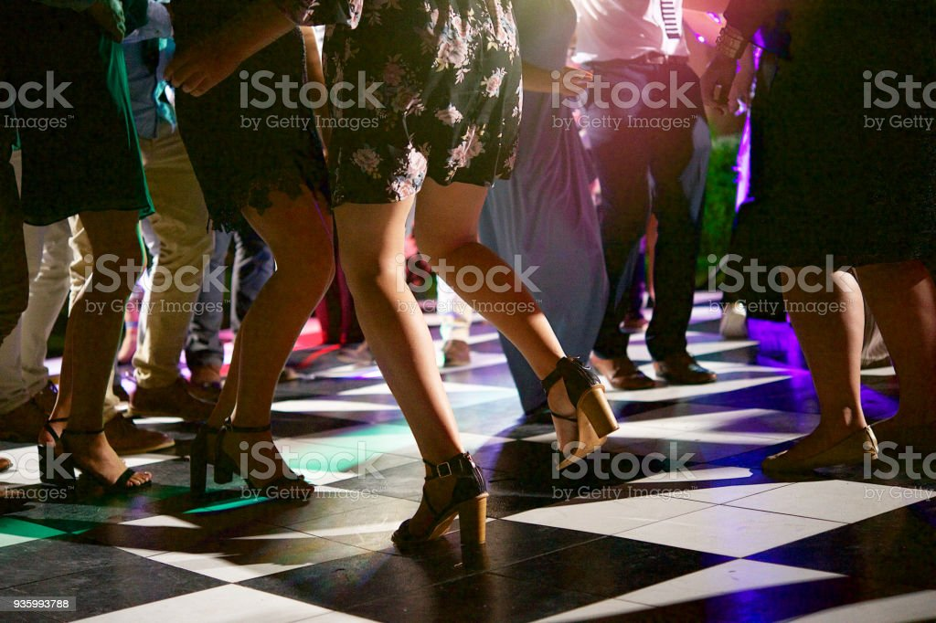 People Dancing on a block shaped dance floor at night outdoors with...