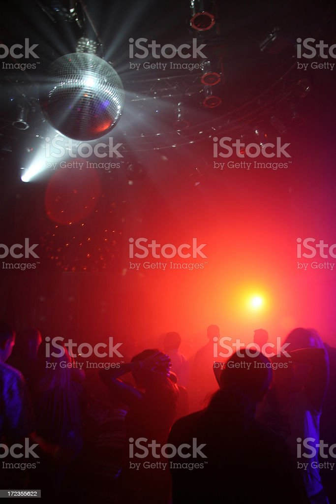 People dancing under a disco ball at a nightclub royalty-free stock photo